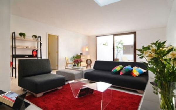 Sofá preto e tapete vermelho complementam a decoração do ambiente