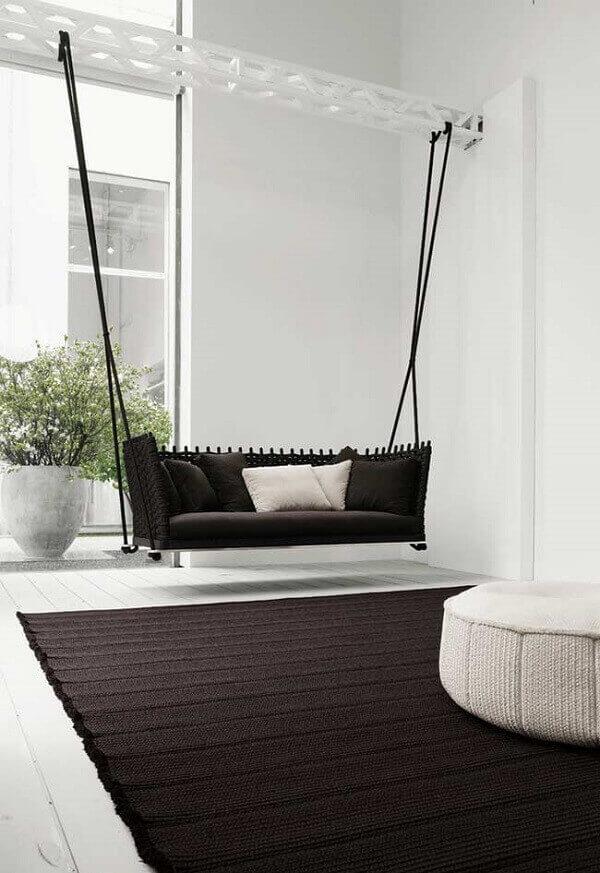 Sofá preto suspenso por cordas e uma viga de ferro no estilo namoradeira