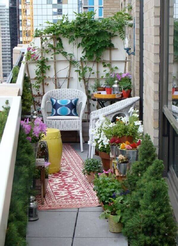 Tapete, almofada e vegetação compõem a decoração da varanda boho