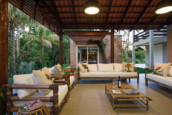 Varanda com móveis de madeira complementam a decoração da casa de chácara