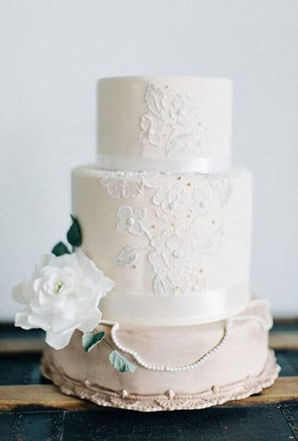 bolo bodas de pérola decorado com renda e flor branca Foto Brides