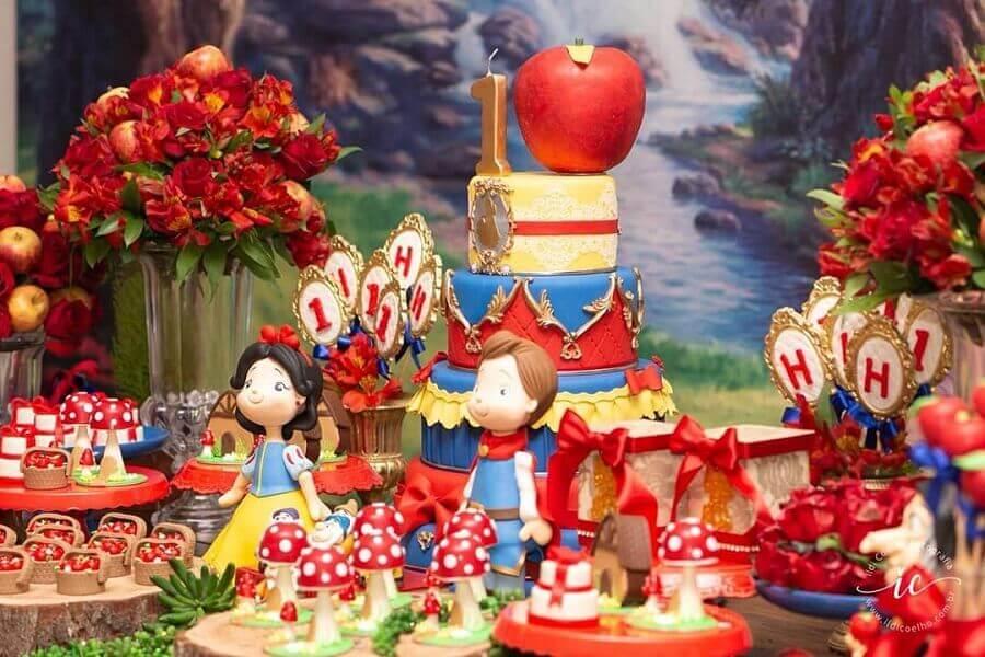 delicada decoração para festa infantil branca de neve com arranjo de flores vermelhas e maças Foto Cida Miyasaki