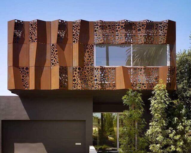 fachada com chapa de aço corten com recortes vazados  Foto Archello