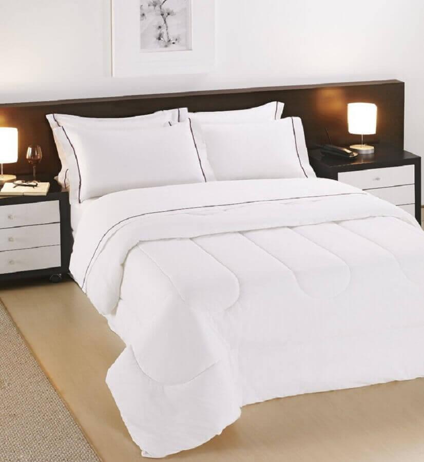 quarto de hotel decorado com roupa de cama branca e pequenos abajures