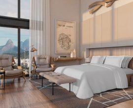 quarto de hotel decorado em cores neutras com amplas janelas