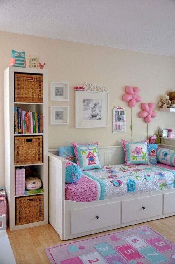 Ambiente lúdico com estante de nicho branco, tapete de amarelinha e cama com gavetas. Fonte: Revista Viva Decora