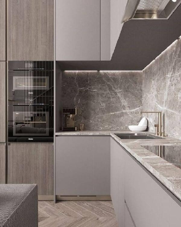 cozinha em l com bancada de pedra cinza e piso de madeira clara