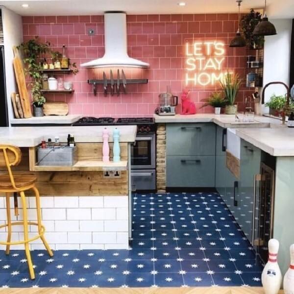 cozinha em l com parede com revestimento vermelho e letreiro neon