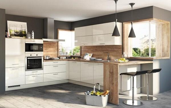 Cozinha em l com armários na cor branca e bancada de madeira