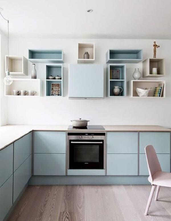 cozinha em l com nichos em tons pastéis e bancada de madeira clara