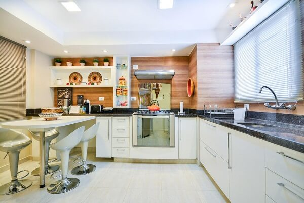 Cozinha em l planejada com pia de granito escuro