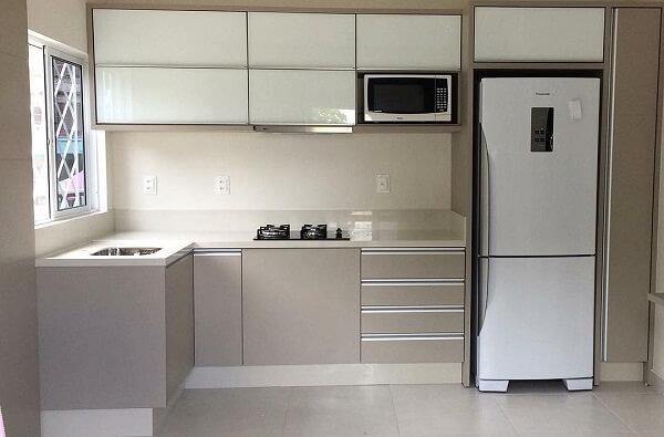 Cozinha em l pequena estrutura com armários em tons neutros