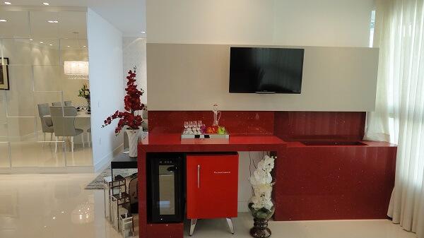 A cor da mini geladeira combina com a pia vermelha trazendo assim harmonia ao ambiente