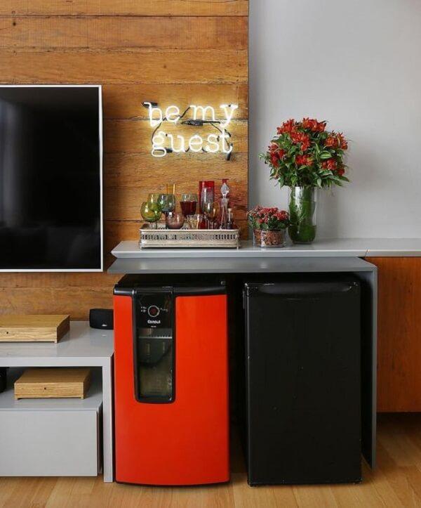 Mini geladeira nas cores laranja e preto complementam a decoração da sala