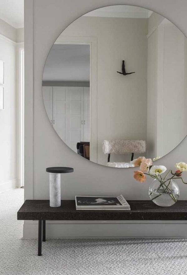 Nesse hall de entrada o espelho redondo quase cobre toda a parede
