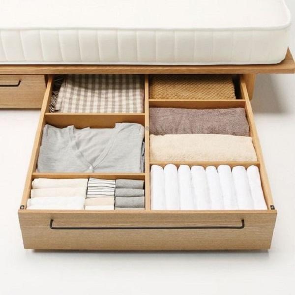 Organize roupas de cama, mesa e banho dentro das gavetas da cama. Fonte: Pinterest
