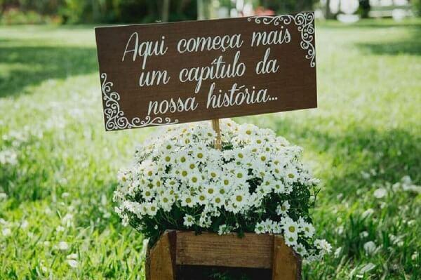 """Plaquinha de casamento com a frase """"Aqui começa mais um capítulo da nossa história..."""""""