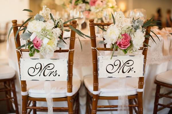 Plaquinhas para cadeira dos noivos e arranjo de flores