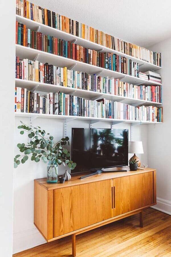 Prateleira de livros acima do rack da sala de estar