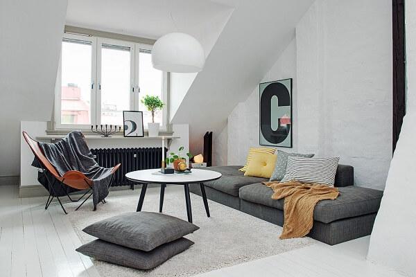 Sótão com sala de estar e decoração em tons neutros e luz natural