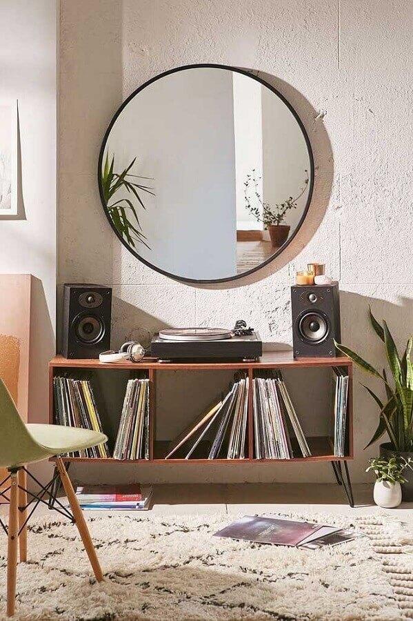 ambiente decorado com estante para discos e espelho redondo Foto Pinosy