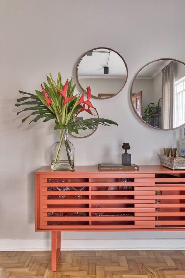 aparador coral decorado com vasos de plantas e espelhos redondos de tamanhos diferentes Foto Casa de Valentina