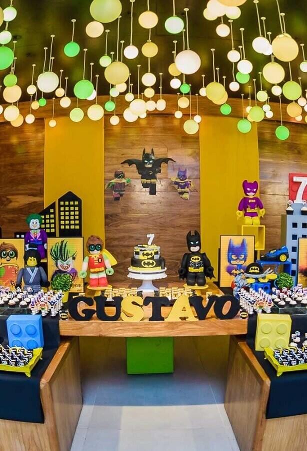 decoração do batman para festa infantil com luminárias redondas no teto e bonequinhos de personagens na mesa Foto Pinterest