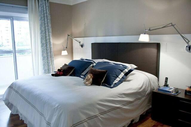 quarto de casal moderno - cama ao lado da janela com almofadas azuis e cabeceira marrom de couro