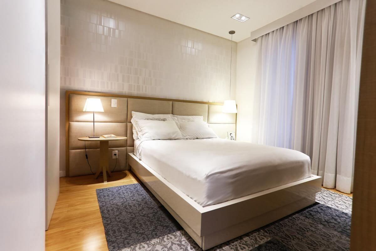 quarto de casal moderno - cama ao lado de cortina e em cima de tapete azul e cinza