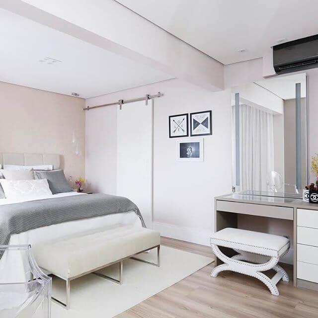 quarto de casal moderno - cama ao lado de porta branca de correr e penteadeira com assento branco estofado