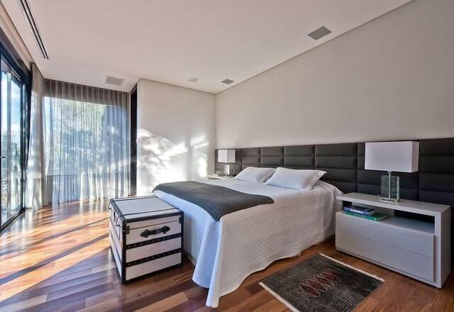 quarto de casal moderno - cama atrás de baú branco e preto e em frente a painel estofado