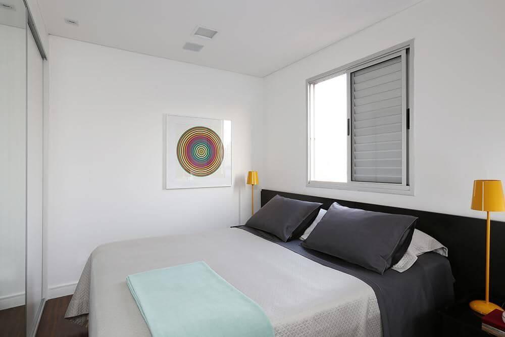 quarto de casal moderno - cama centralizada, com janela branca atrás e abajur amarelo ao lado