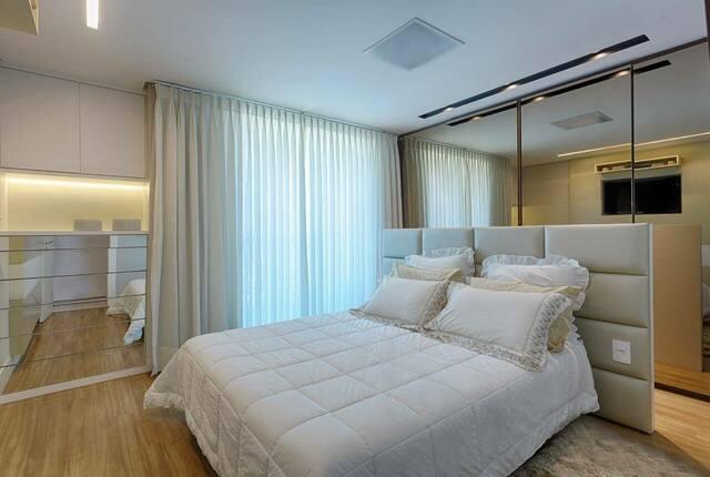 quarto de casal moderno - cama centralizada, com travesseiros com babados em frente a uma cabeceira estofada e parede de espelhos