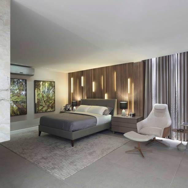 quarto de casal moderno - cama centralizada, em frente a painel de madeira iluminado