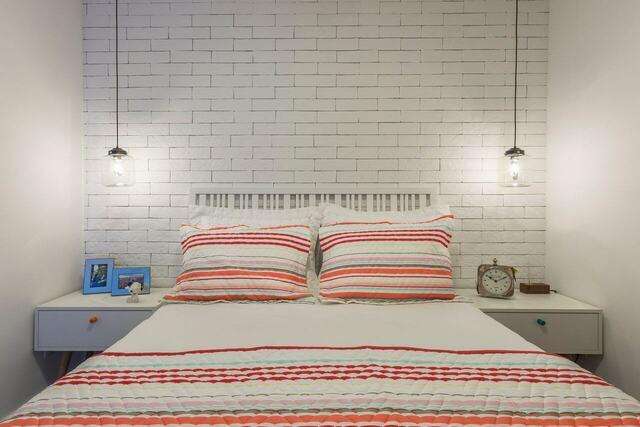 quarto de casal moderno - cama centralizada, em frente a parede de tijolos brancos com duas luminárias de teto