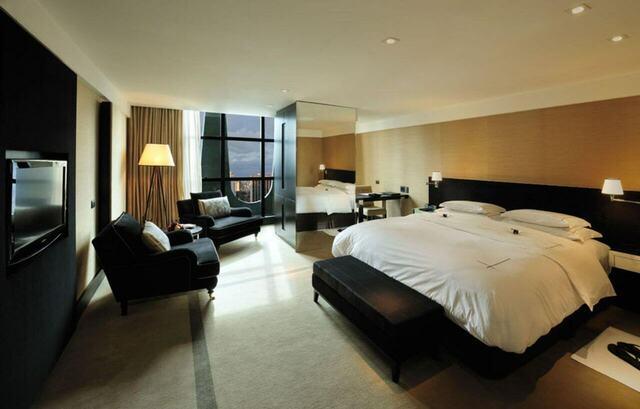 quarto de casal moderno - cama com lençóis brancos em frente a poltronas pretas