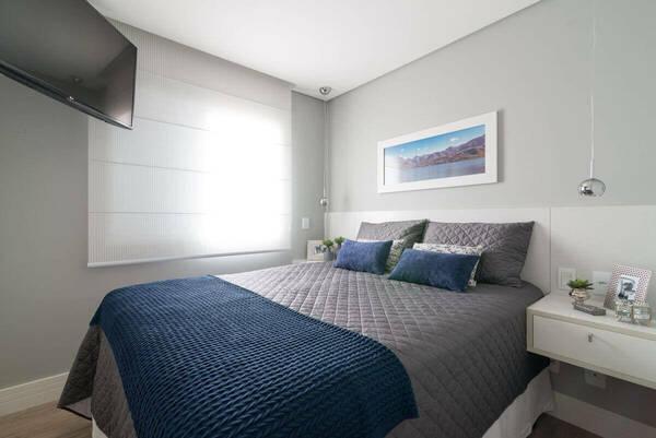 quarto de casal moderno - cama com lençois azul e cinza em frente de tv afixada na parede