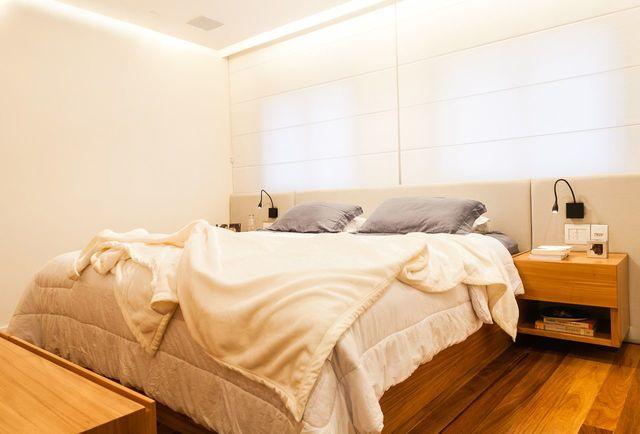 quarto de casal moderno - cama em cima de piso laminado com criado mudo de madeira