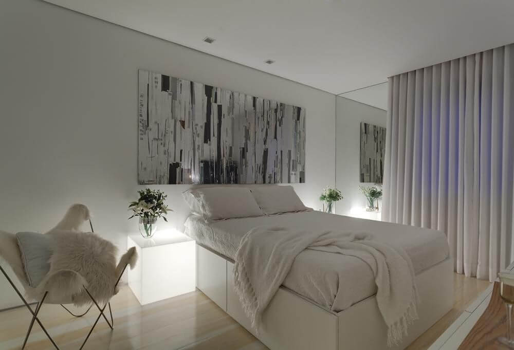 quarto de casal moderno - cama em frente à quadro abstrato e ao lado de mesa iluminada