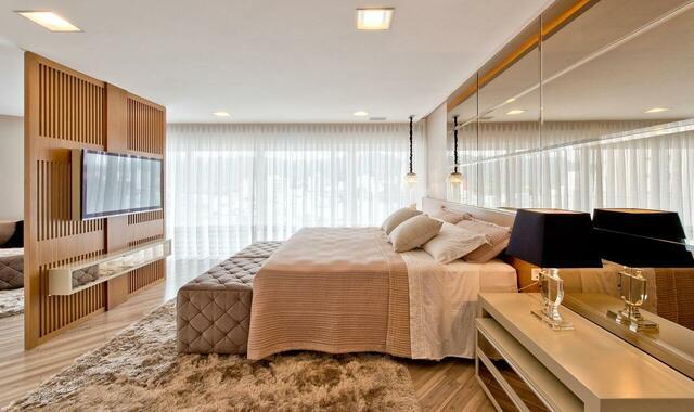 quarto de casal moderno - cama em parede de espelhos em frente a uma parede de madeira com televisão afixada