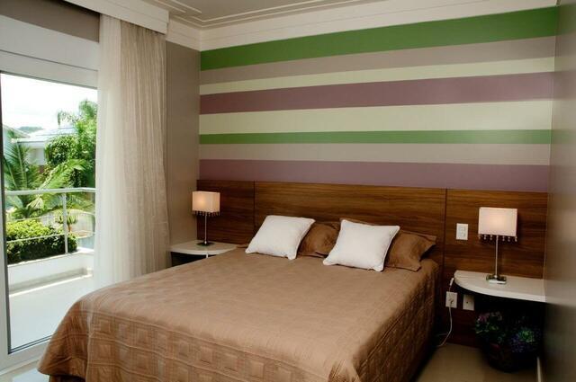 quarto de casal moderno - cama em placa de madeira e parede pintada com faixas verdes, brancas e roxas