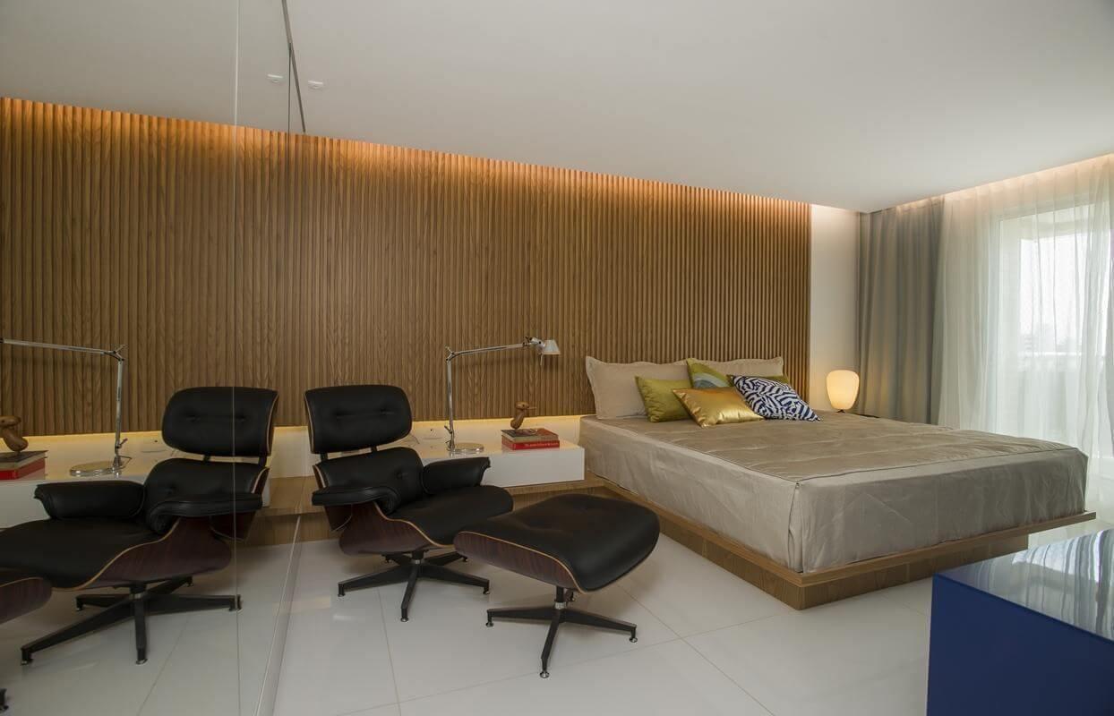quarto de casal moderno - cama sem cabeceira ao lado de poltrona preta