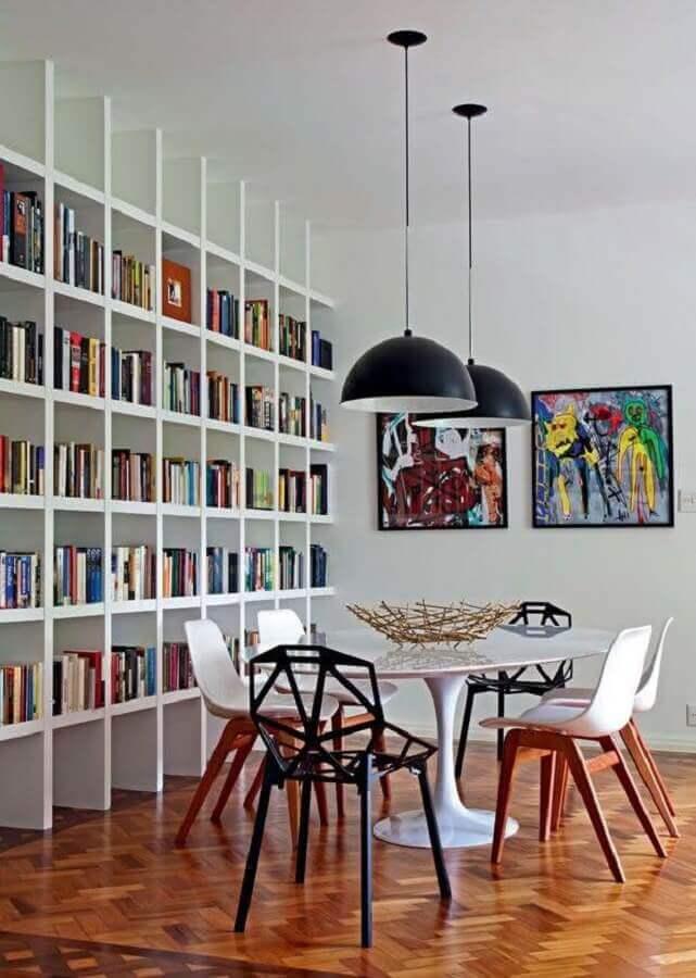 sala de jantar decorada com estante para livros vazada Foto Casa Pensada