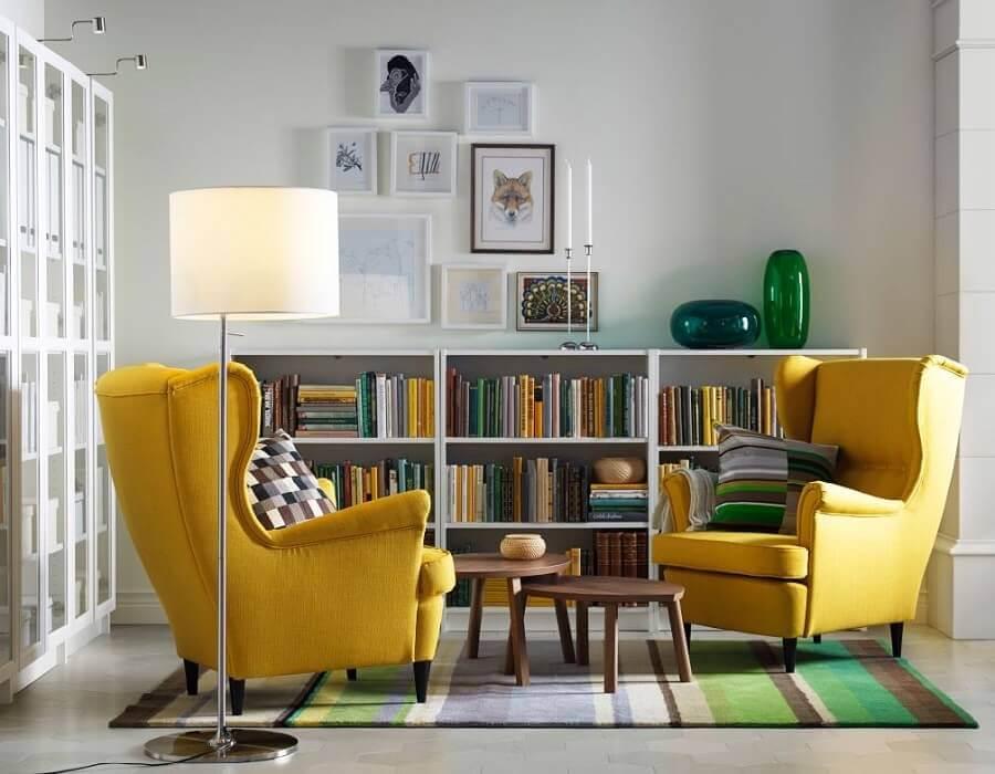 sala decorada com estante pequena para livros e poltronas amarelas Foto Pinosy