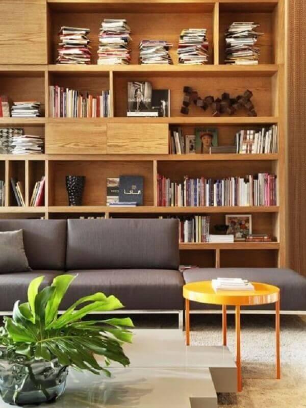 sala decorada com sofá cinza e estante de madeira para livros Foto FRISO – Arquitetura e Interiores