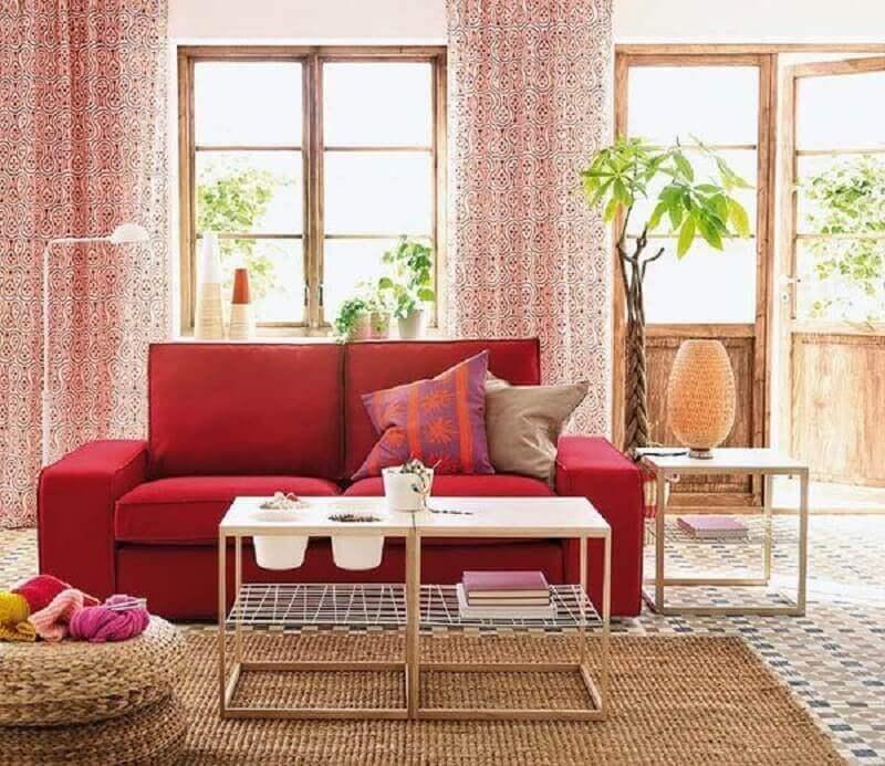 sala decorada com sofá vermelho e puff de pneu