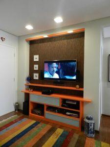 tinta para madeira - quarto com painel de televisão laranja
