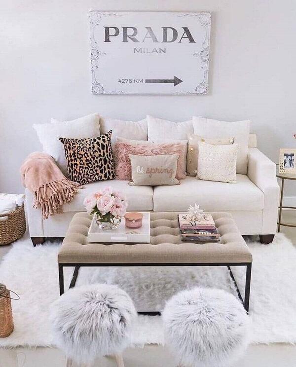 A decoração da sala de estar mescla as cores rosa e dourado