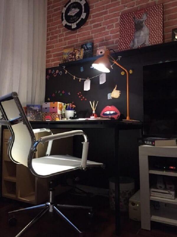 A escrivaninha preta combina a decoração do quarto de solteiro