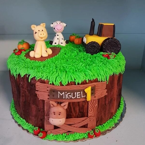 The little farm party is represented in the cake with grass, tractor, wooden fence and animals